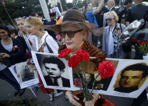 A woman holds a pictures of her relatives killed in WWII, during the Victory Day ceremony, in Belgrade, Serbia, Monday, May 9, 2016. People flocked to memorial cemetery to the liberators of Belgrade marking the 71th anniversary of the victory over Nazi Germany in WWII. (AP Photo/Darko Vojinovic)