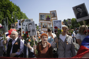 People show posters of Soviet World War II soldiers as they march to lay down flowers at a Russian War Memorial to commemorate the end of World War II 71 years ago, at the district Tiergarten in Berlin, Germany, Monday, May 9, 2016. (AP Photo/Markus Schreiber)