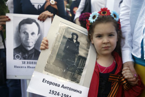 A girl holds a picture of her relative killed in WWII, during the Victory Day ceremony, in Belgrade, Serbia, Monday, May 9, 2016. People flocked to memorial cemetery to the liberators of Belgrade marking the 71th anniversary of the victory over Nazi Germany in WWII. (AP Photo/Darko Vojinovic)